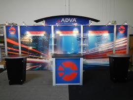 RENTAL:  RE-2009 Arch Canopy, Halogen Arm Lights, RE-1202 Counter, (2) RE-1201 Counters, and Clear Acrylic Shelves. Tension Fabric Graphics, and Sintra Header and Counter Graphics -- Image 1
