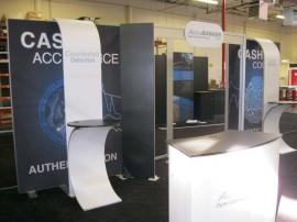 eSmart Custom Exhibit with Aluminum Extrusion Frame, Laminate Shelves, Sintra Header Graphics, SEG Fabric Fraphics, LED Luminators, Custom Podium, and Monitor Mounts. Converts to 10x10 -- Image 1