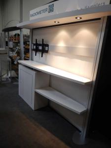 "RENTAL: RE-1019 with White Laminated Sconce with Puck Lighting, RE-1201 Tapered Counter, White Laminated Backwall Counter & Shelves, Large Monitor Mount, 42"" Monitor, RE-171 Literature Stand, Tension Fabric Panel for Backwall, Sintra Header Graphic, and V"