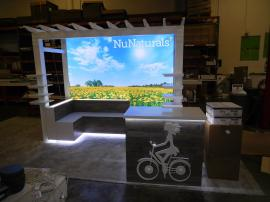 Custom Exhibit with Pergola, Product Shelves, Benches, LED Lightbox, Perimeter Accent Lights, and Counter with Storage and Standoff Graphic