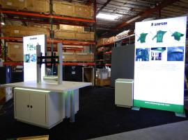 "RENTAL: Custom Island Design with (2) 60"" Wide x 120"" High Double-Sided Lightboxes, Custom Products Table with Recessed LED Lighting, (2) Large Monitor Mounts, (2) 2' x 2' Custom White Laminated Pedestals with Recessed LED Lighting, SEG Backlit Fabric Gra"