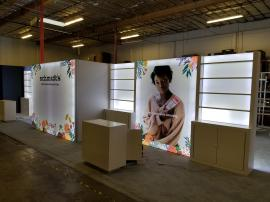 Custom Inline Exhibit with Extensive Shelving, Backlighting Including Backlit Graphics, Locking Storage, Full Closet, and Reception Counters