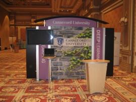 RENTAL Exhibit -- Pavilion with multiple 10' exhibits, arch-shape canopies with black covers, Sintra accent wings, tapered counter workstations, 16' high exhibits, kiosks -- Image 1